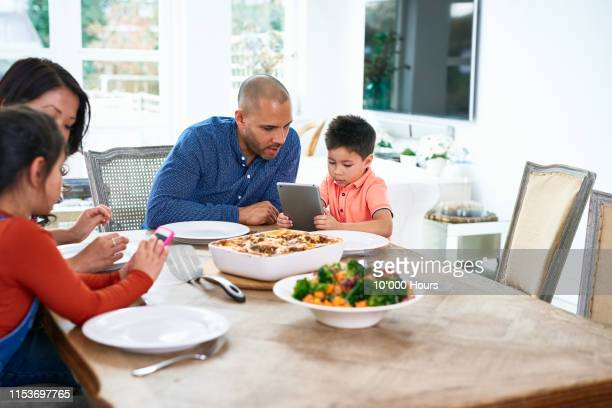 father looking at son using digital tablet at dinner table - filipino family dinner stock pictures, royalty-free photos & images