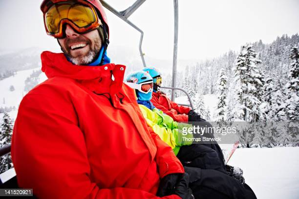 father looking back sitting on chair lift - ski lift stock pictures, royalty-free photos & images