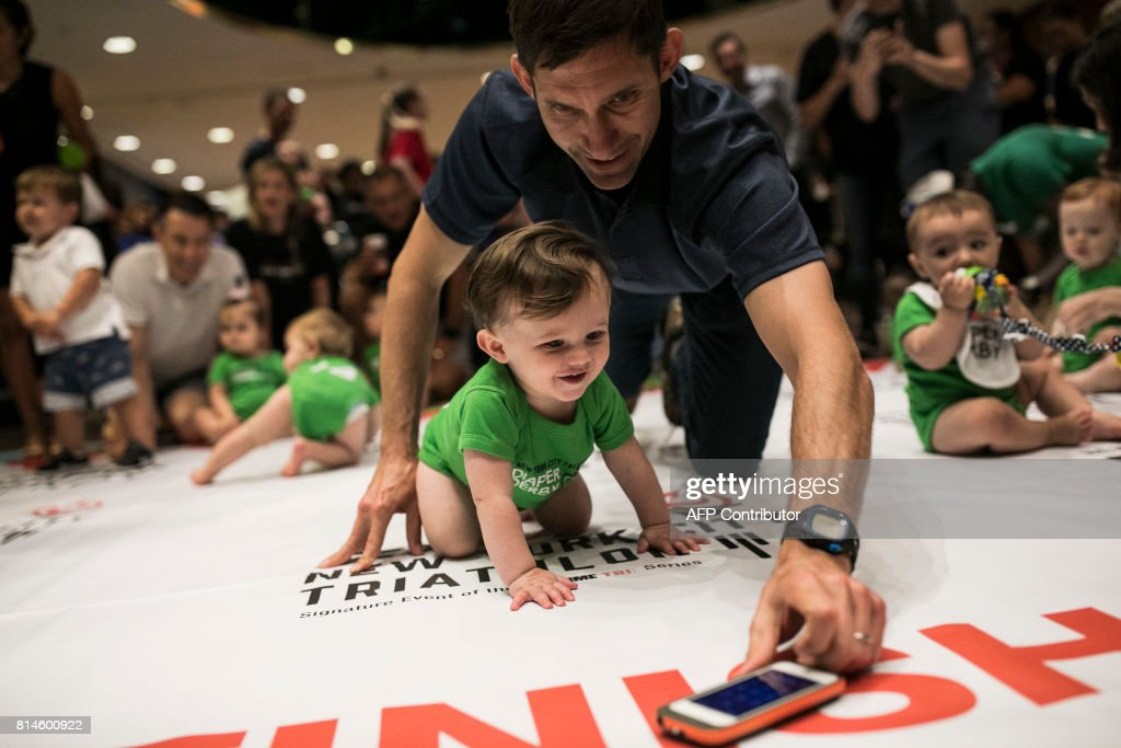 A father lures his child along with an iPhone during warmups before babies race in the NYC Triathlon's annual Diaper Derby, July 14, 2017, in New York City. Around 30 infants raced in several heats across a 12-foot course as their parents urged them on from either end. /