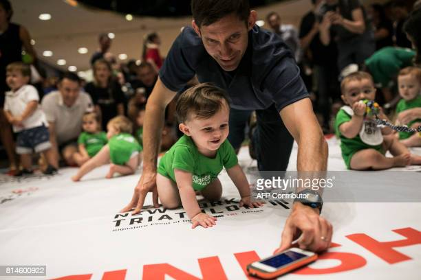 A father lures his child along with an iPhone during warmups before babies race in the NYC Triathlon's annual Diaper Derby July 14 in New York City...