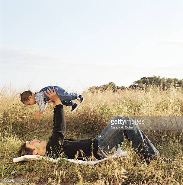 Father lying on back in field, holding baby boy (6-9 months) above him