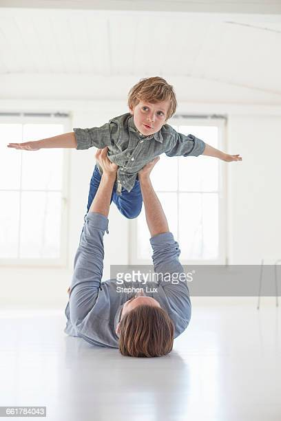 father lying on floor holding up son - voler photos et images de collection