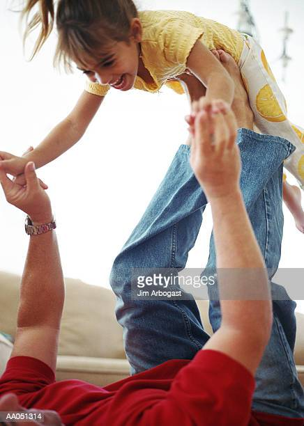 Father lying on floor, lifting daughter (4-6)