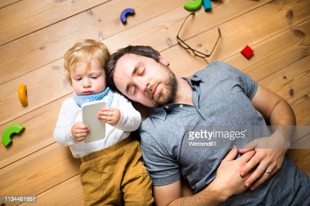 father lying on floor with his little son playing with smartphone - neonati maschi foto e immagini stock