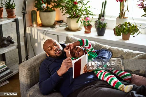 Father lying on sofa with son reading book