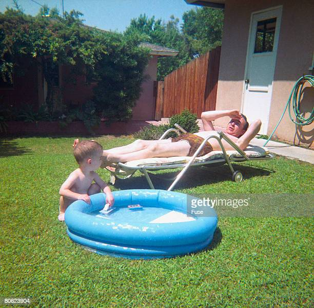 father lying on sun lounger in the garden, little son at paddling pool - 1960 stock pictures, royalty-free photos & images