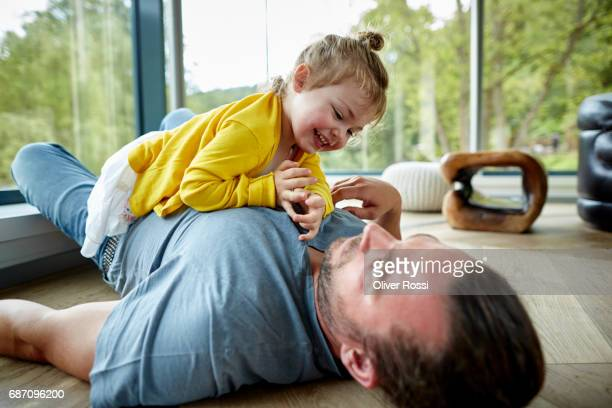 father lying with little daughter on the floor - topknot stock pictures, royalty-free photos & images