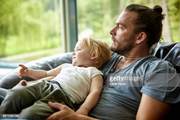 Father lying with little son on the couch