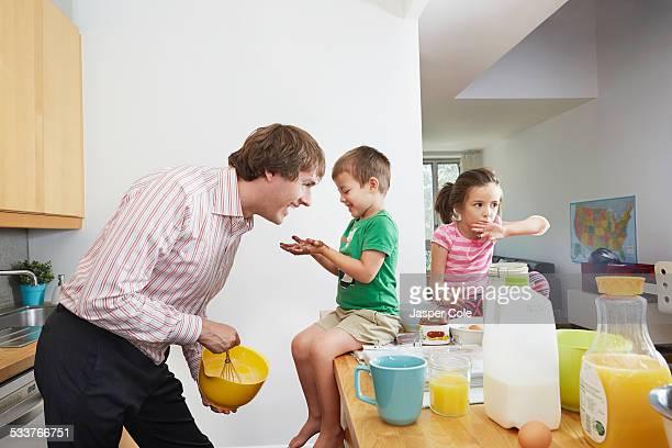 Father making breakfast for children in kitchen