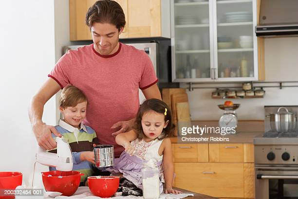 Father making cakes with son and daughter (2-6)