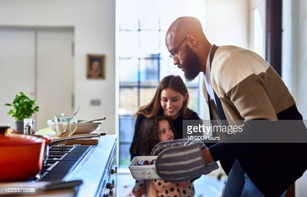 father making dinner with mother and daughter at home - 週末の予定 ストックフォトと画像