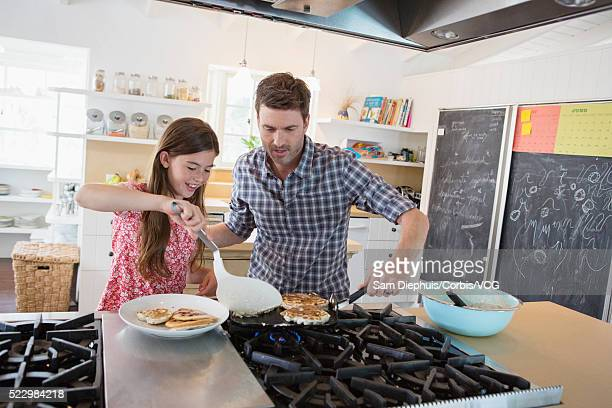 Father making pancakes with daughter (10-12)