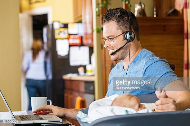 Father making phone calls while caring for baby daughter