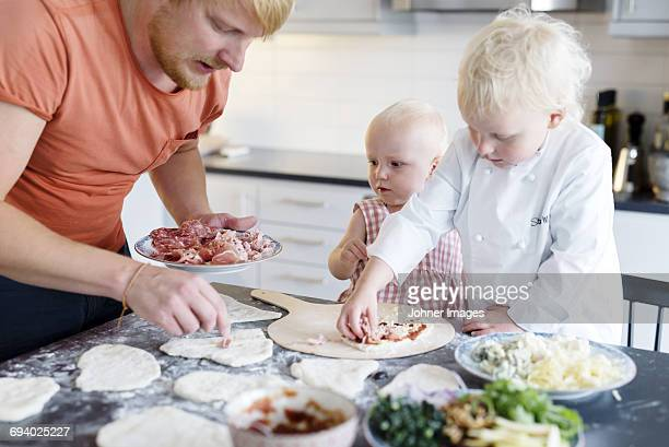 Father making pizza with sons