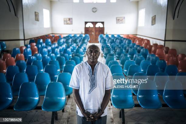 Father Marc Kanamugire Gakara poses for a photograph in the Catholic parish of the Holy Spirit deserted by the parishioners on the morning of March...