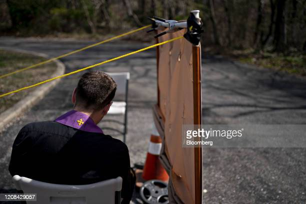 Father Matthew Fish waits for penitents at a drive thru confessional, set up in response to the coronavirus pandemic outside Holy Family Catholic...