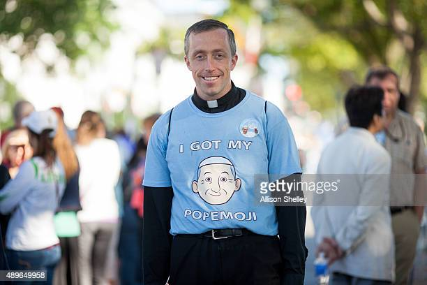 Father Matthew Schneider poses for a portrait in his 'Popemoji' tshirt as spectators gather around the Ellipse to catch a glimpse of Pope Francis...