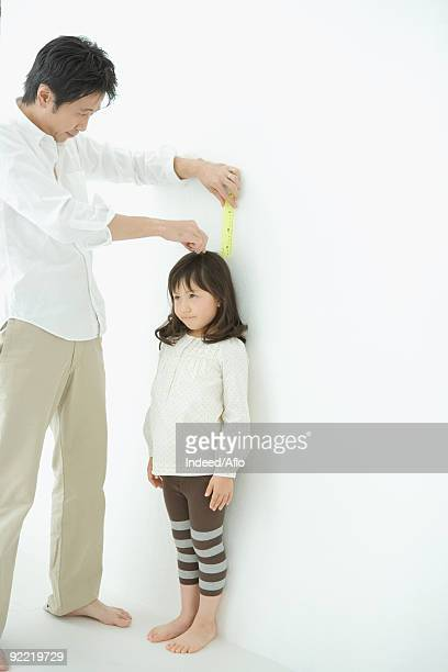 Father measuring daughter height on wall