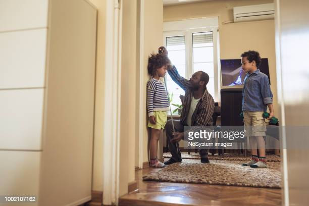 father measuring daughter height - measuring stock pictures, royalty-free photos & images