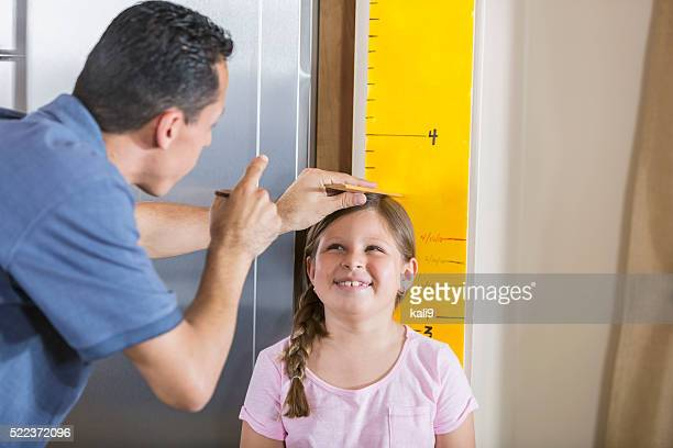 Father measuring girl's height on growth chart