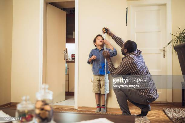 father measuring sons height - measuring stock pictures, royalty-free photos & images