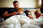 Father measuring temperature of his sick son