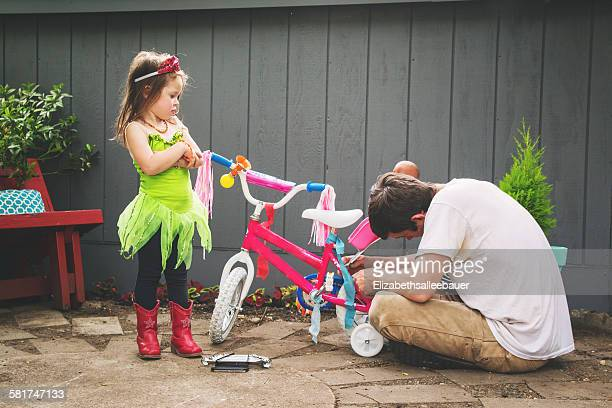 Father mending his daughter's bicycle