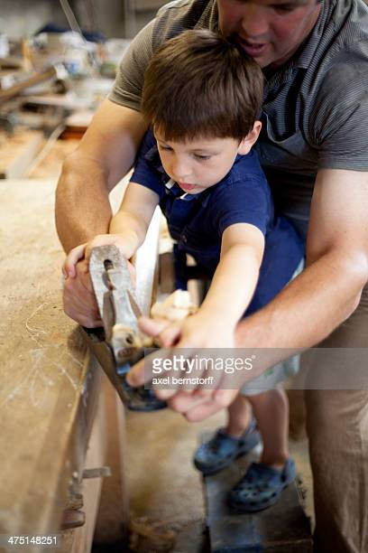 Father mentoring son on carpentry in boat  workshop