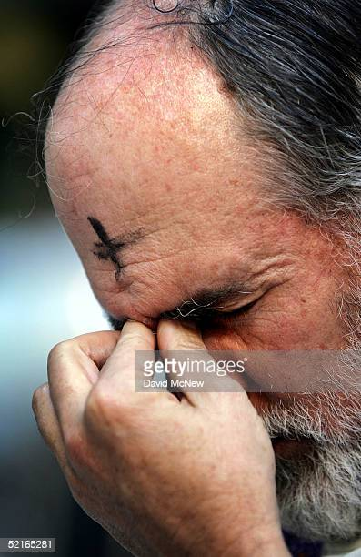 Father Michael Kennedy wears an ash cross on his forehead as he prays at an interfaith Ash Wednesday service to pray for the future of Iraq and call...