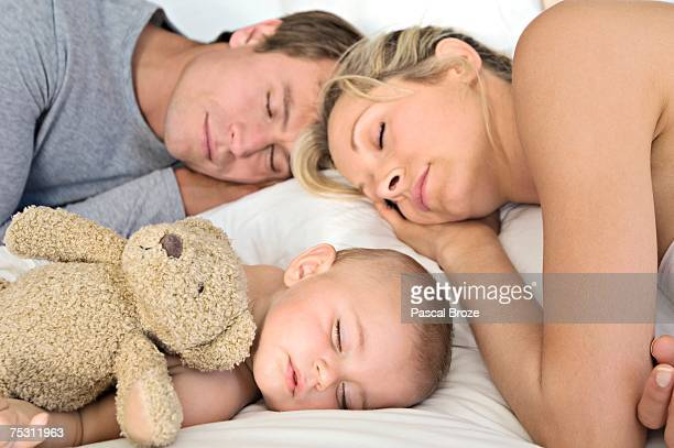 Father, mother and baby sleeping, indoors