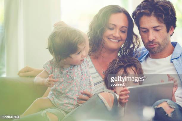 Father, Mother and children with digital tablet.