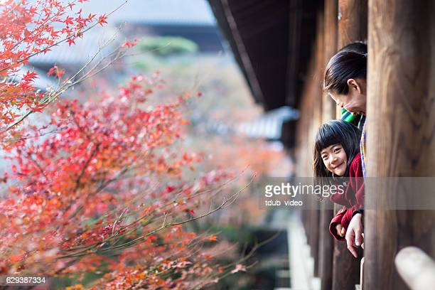 Father, mother and daughter at a temple enjoying autumn leaves