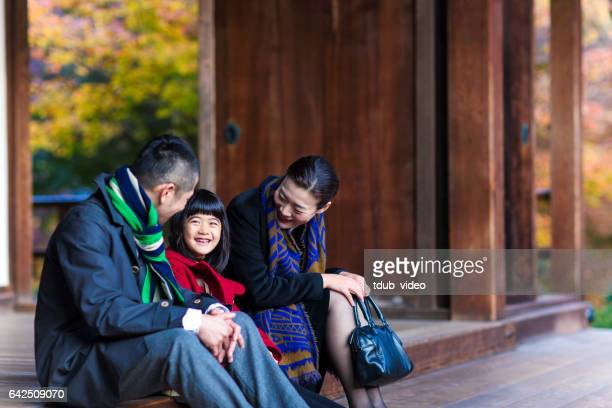 father, mother and daughter sat relaxing at a temple - tdub_video stock pictures, royalty-free photos & images
