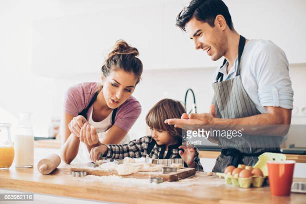 Father, mother and son making cookies together