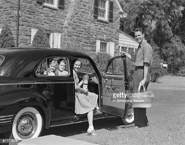 Father Mother Boy & Girl Smiling Dad Is Standing With Hand On Open Car Door Holding A Basket Mom Is Sitting In Front Seat Holding A Thermos Kids Back.
