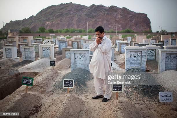 Father Muhammad Munawar prays at the grave of his slain son, 17-year-old medical student Waleed July 14, 2010 in Chenab Nagar, Pakistan....