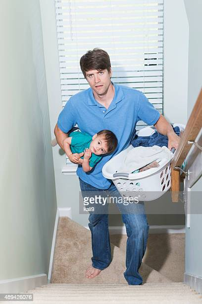 Father multitasking, carrying baby and laundry upstairs
