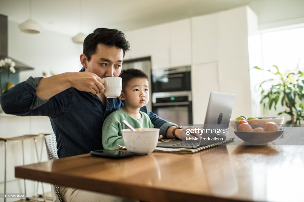 Father multi-tasking with young son (2 yrs) at kitchen table : Stock Photo