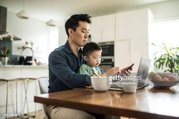 father multi-tasking with young son (2 yrs) at kitchen table - websurfen stock-fotos und bilder