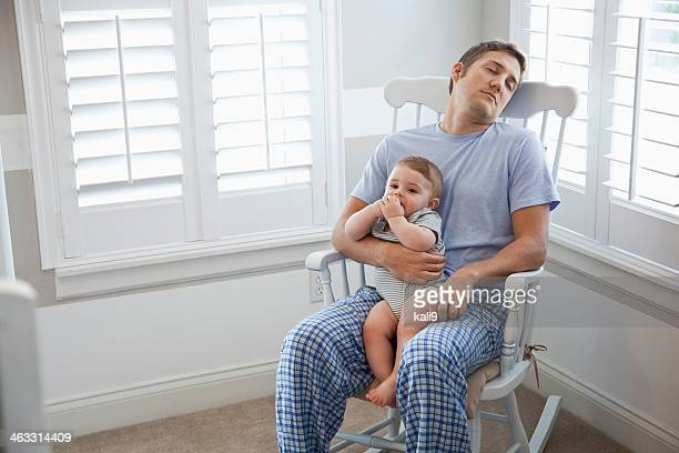Father napping with baby in lap
