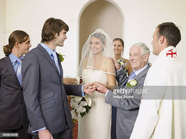 Father of bride giving daughters hand to groom