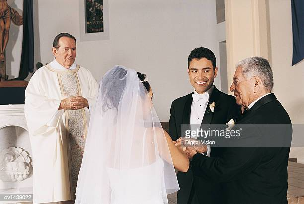 Father of the Bride Gives her Hand in Marriage to the Groom at the Altar