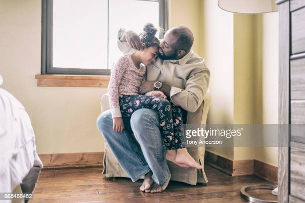 Father on chair at home with daughter on his lap.