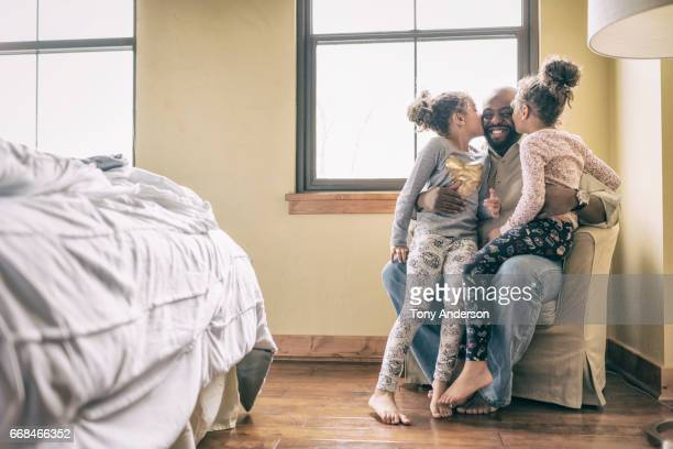 Father on chair at home with twin daughters on his lap