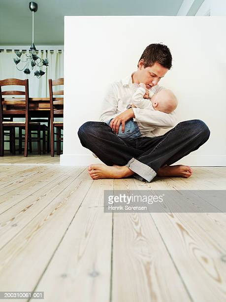 Father on floor feeding baby son (3-6 months) with bottle, ground view
