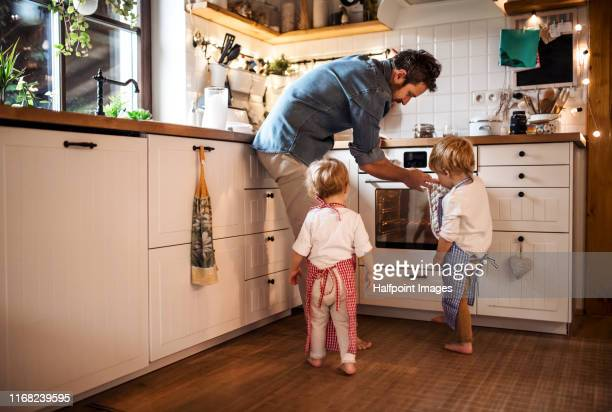 a father on paternity leave baking with two children indoors. - homemaker stock pictures, royalty-free photos & images