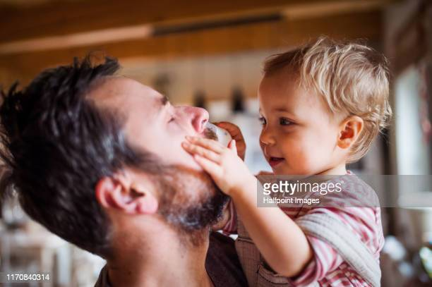 a father on paternity leave looking after small daughter indoors, using nasal spray. - paternity leave stock pictures, royalty-free photos & images
