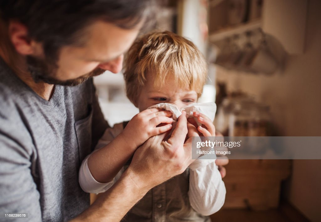 A father on paternity leave looking after small son indoors, blowing his nose. : Stock Photo