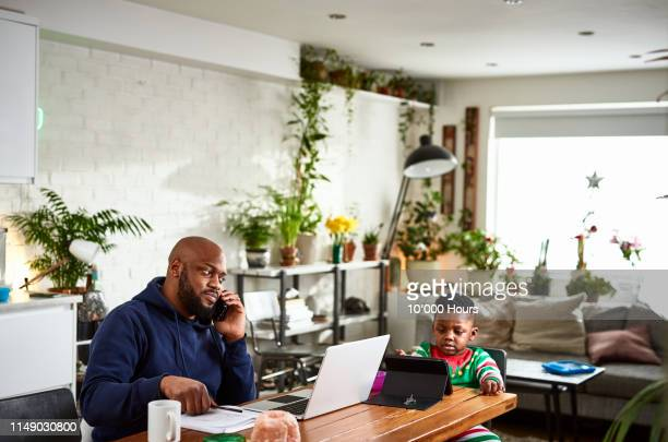 father on phone call and working with son watching tablet - genderblend stock pictures, royalty-free photos & images