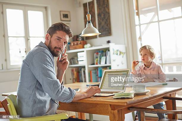 Father on phone while working in home office with son